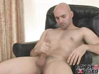 Dirty bald gay Bucky jerking his monster cock on the armchair