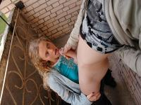 Young golden-haired sucking on the veranda