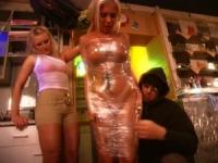 Teen minx wrapped naked in plastic cellophane