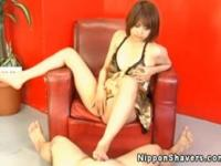Shaved asian in lingerie giving footjob