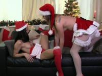 Lesbians in Santa Claus costumes finger on the sofa