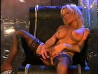 Hot, busty blonde babe sits in her chair toying her clit away