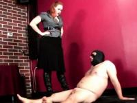 Tattooed dominatrix on heels torturing cock