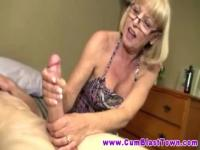 Older mum is jerking her younger fucker's penis
