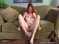 Redhead Aurora Rose strokes an ebony dong with her feet