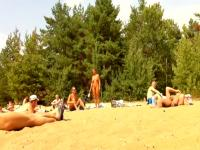 Wives and their husbands sunbathing at the nudist beach